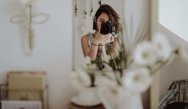 decorativa en fotografía para organizadores profesionales. Se ve una chica con una cámara de fotos en disposición de fotografiar un interior